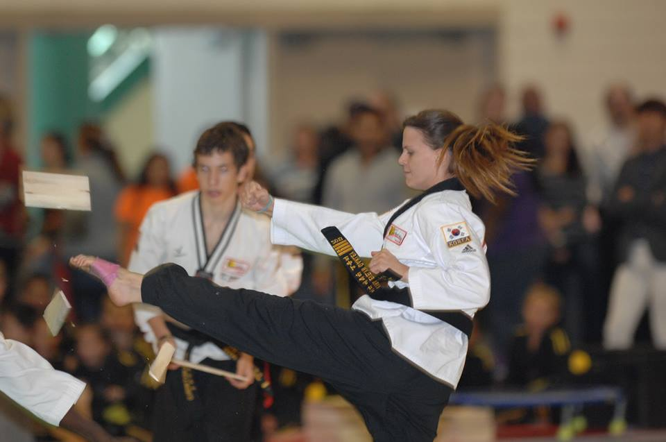 Master Kyra Oakley performs a spinning mid air kick while holder performs back flip