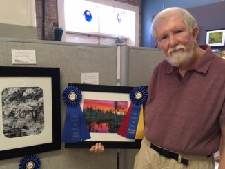 "Jim Liestman with his photos ""Serenity"" and ""Wetland Sunset"" at the Franklin County Arts Council Gallery, Franklinton NC. Source: Donna Campbell Smith."