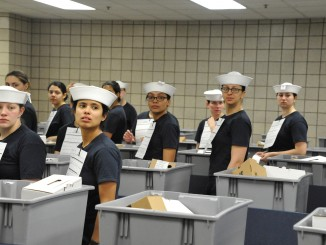 "April 4, 2016 - Female seaman recruits receive their white enlisted hats, or ""Dixie Cups,"" during uniform issue at Recruit Training Command. These women were among the first recruits to be issued the Dixie cup as part of the Navy's efforts for uniformity in service members' uniforms. (US Navy photo by Sue Krawczyk/Released)."