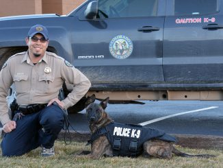 Sci, a CPW K9, in armor is shown with a handler. Source: Kyle Davidson, Colorado Parks and Wildlife.
