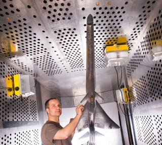 Mechanical technician Dan Pitts prepares a nine percent scale model of Lockheed Martin's Quiet Supersonic Technology (QueSST) X-plane preliminary design for its first high-speed wind tunnel tests at NASA's Glenn Research Center in Cleveland. Credits: NASA