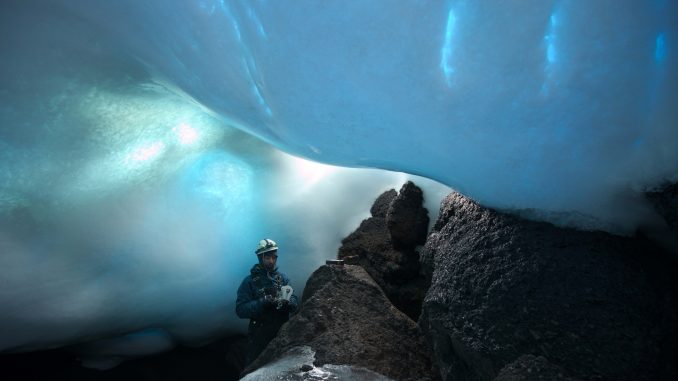 Aaron Curtis, a post-doctoral scholar at JPL, measures gases inside an ice cave. Carbon dioxide levels can be especially high inside the caves, so gas monitors are necessary for safety. Image: Dylan Taylor.