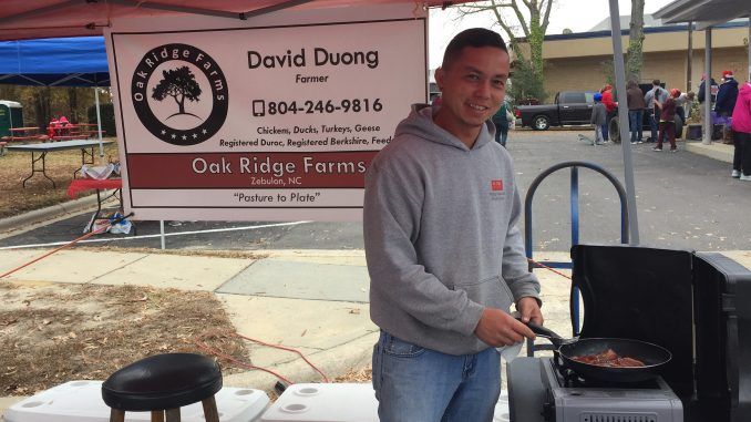 Oak Ridge Farms' David Duong serving bacon samples at the Zebulon Pop-up Vendor Market, December 2, 2017. Photo: Kay Whatley