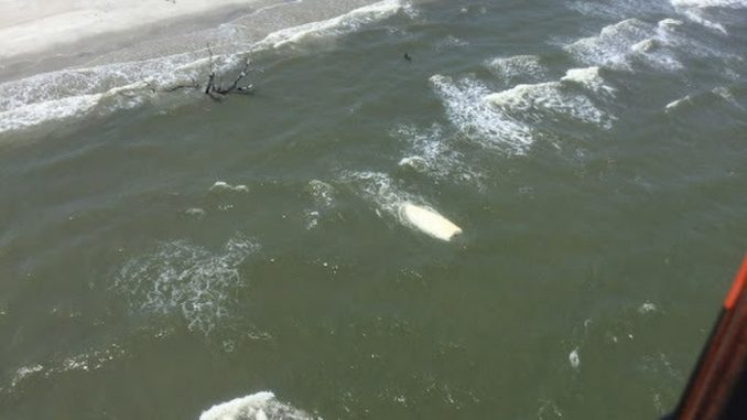 Coast Guard Air Station Savannah MH-65 Dolphin helicopter crew rescues three boaters after their vessel capsized June 19, 2018. Source: US Coast Guard photo courtesy of Air Station Savannah