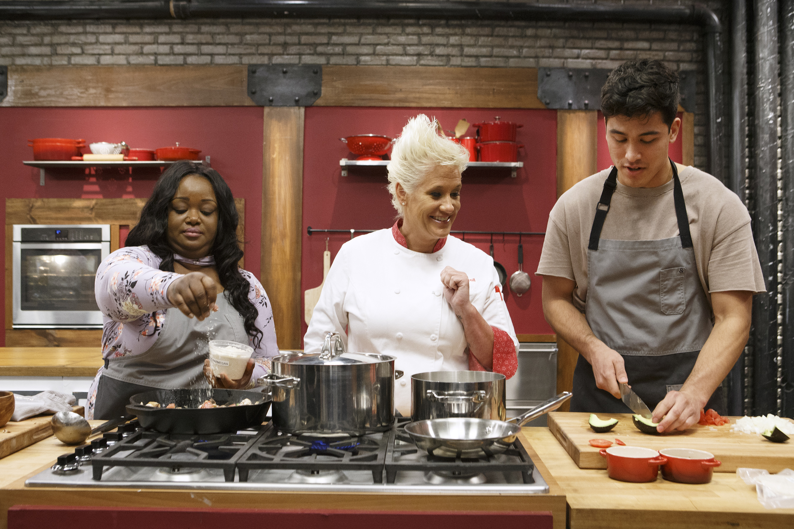 Mentor Anne Burrell checks in on recruits Janese Henry and Bradley Garcia as they cooks during the baseline challenge, as seen on Worst Cooks in America, Season 14. Source: Daniela Medina, Allied Integrated Marketing