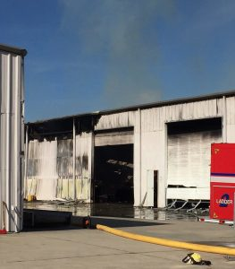 View between warehouses, with fire continuing inside the right-side building. Photo: Kay Whatley