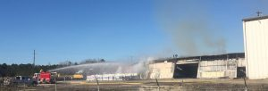 Fire crew dousing the burning warehouse. Photo: Kay Whatley