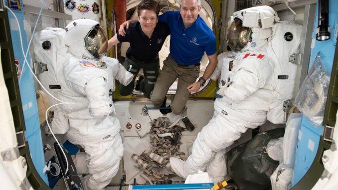 Astronauts (from left) Anne McClain and David Saint-Jacques are pictured in between a pair of spacesuits that are stowed and serviced inside the Quest airlock where U.S. spacewalks are staged. Credits: NASA
