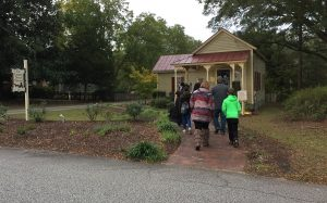 Tour group approaching The Country Doctor Museum, led by a costumed volunteer. Photo: Kay Whatley