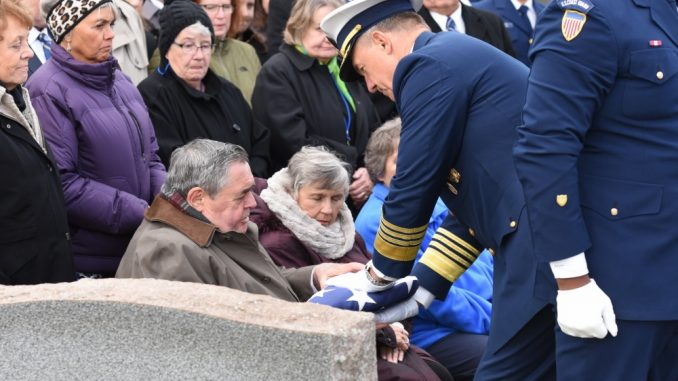 Admiral Karl Schultz, Commandant, US Coast Guard, presents a flag to Patrick Crotty, Lt. Crotty's nephew, during the graveside ceremony, Buffalo, New York, Nov. 2, 2019. Crotty, a USCG POW, was recently identified by the Defense POW/MIA Accounting Agency and brought back to Crotty's hometown of Buffalo for burial in a family plot. Source: US Coast Guard photo by Petty Officer 3rd Class Brian McCrum