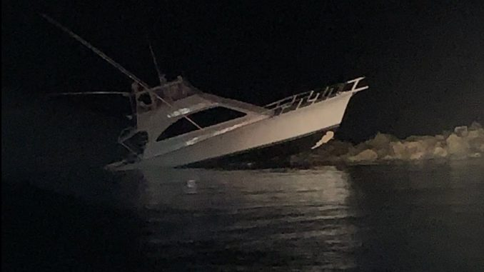 The Strike Finder, a 52-foot sport fisher, rests on rocks after alliding with the southern Charleston jetty March 22, 2020, in Charleston, SC. Photo: US Coast Guard