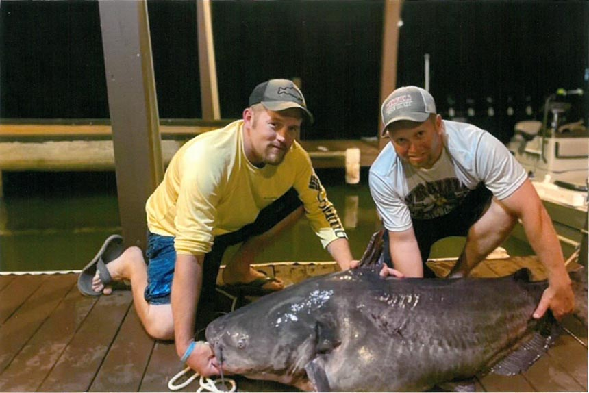 Mark Conroy (left) and Joey Baird with Baird's 121-pound, 9-ounce blue catfish caught in Six Pound Creek at Lake Gaston. Source: NC Wildlife